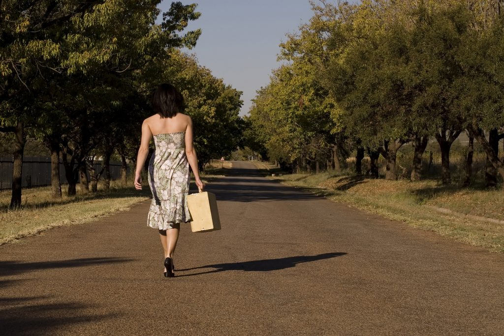 Brunette walking away from camera down tree lane with suitcase -freedom and wealth